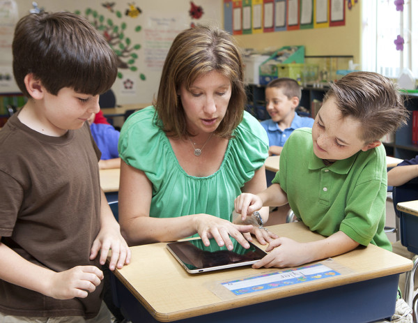 kids learning using tablet / ipad with teacher
