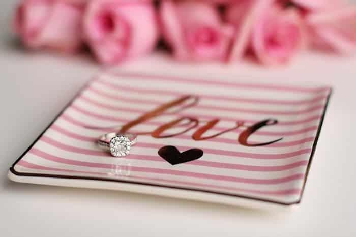 diamond ring on a dish that says love fake diamonds