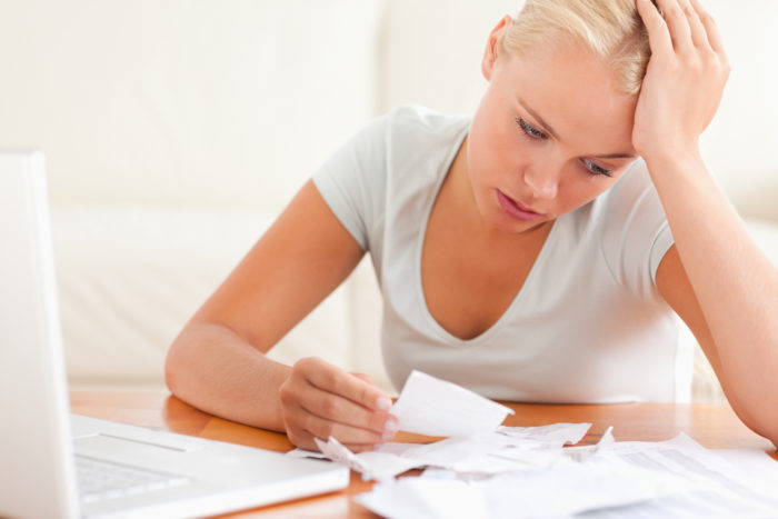 How to heal your financial mistakes... woman worrying over bills and money
