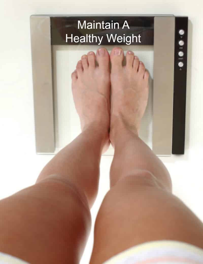 Standing on bathroom scales to maintain a heart healthy weight.